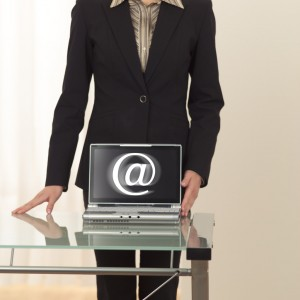 "Businesswoman With Laptop and ""At"" Sign"